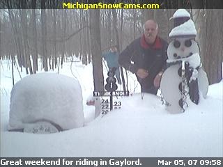 Snowcam picture of Jack Aumann standing next to the snowman.