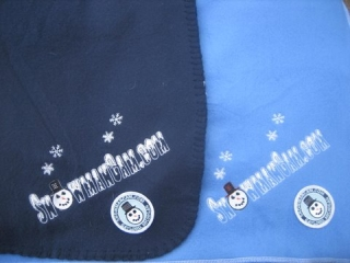 Snowman Cam blankets are available in light blue or navy blue. Snowman Cam logo and snowflakes are embroidered. Also had a Snowman Cam patch sewn on.